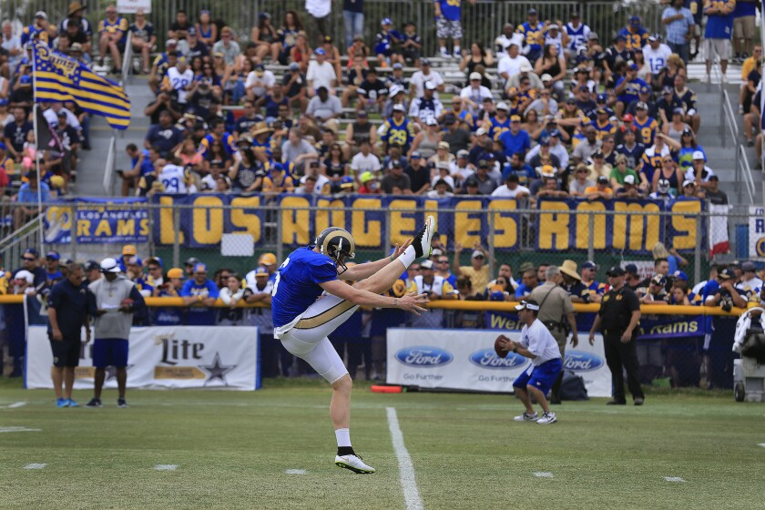 St. Louis punter Johnny Hekker gets off a kick with a Los Angeles Rams banner in the background during a combined practice session with the Dallas Cowboys.