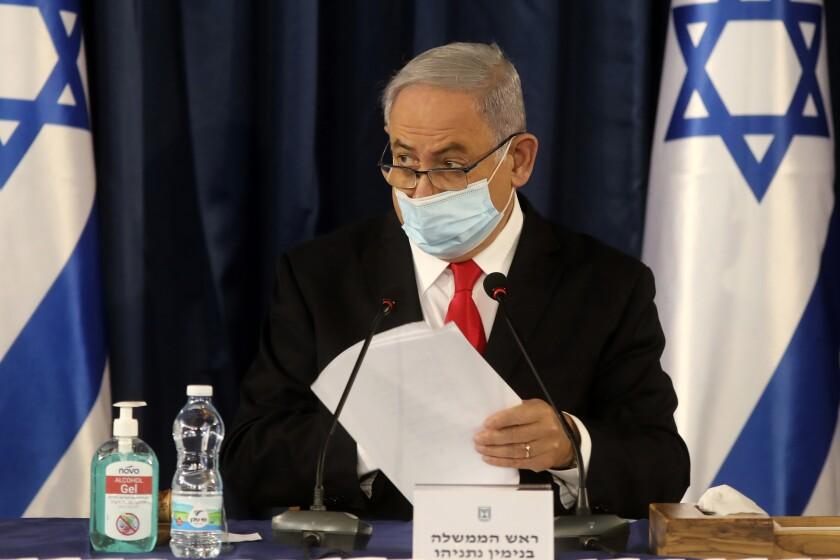 Israeli Prime Minister Benjamin Netanyahu, wearing a protective mask due to the COVID-19 pandemic, chairs the weekly cabinet meeting in Jerusalem, Sunday, June 7, 2020. (Menahem Kahana/Pool Photo via AP)