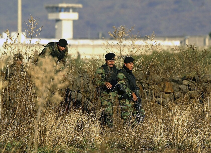 """FILE - In this Jan. 28, 2005 file photo, Mexican Army soldiers inspect the surrounding the top-security Puente Grande prison, on the outskirts Guadalajara City, Mexico. The Mexican government announced Monday, Sept. 28, 2020, that it will close the Puente Grande federal prison made famous by the 2001 escape of convicted drug lord Joaquin """"El Chapo"""" Guzman. (AP Photo/Guillermo Arias, File)"""