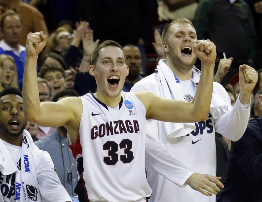 FILE - In this March 22, 2015, file photo, Gonzaga's Kyle Wiltjer (33) and Przemek Karnowski, right, celebrate in the final seconds of the second half of an NCAA tournament college basketball game against Iowa in the Round of 32, in Seattle. No. 9 Gonzaga returns a talented front court of Wiltjer,