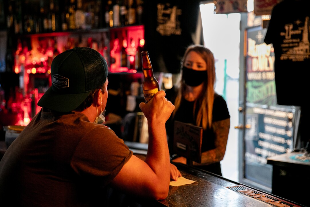 Chad Walery, 46, of City Heights, drinks a beer at The Tower Bar while talking to bartender Christina Hankins