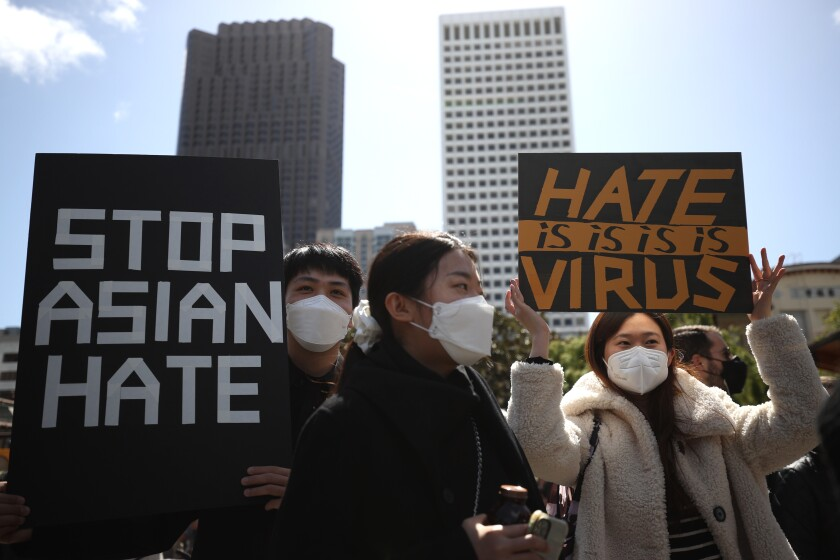 """People hold signs that say """"Stop Asian hate"""" and """"Hate is virus."""""""