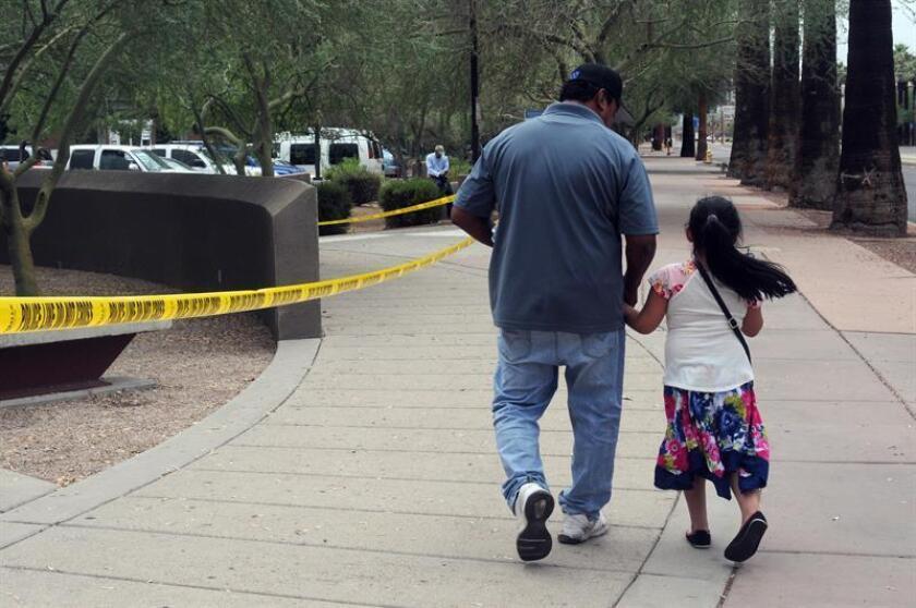 Un hombre camina junto a su hija tras salir de una cita en la Oficina de Control de Inmigración y Aduanas (ICE), desde donde supuestamente se transportará a los menores de 5 años liberados para reunificarlos con sus padres. EFE/Archivo