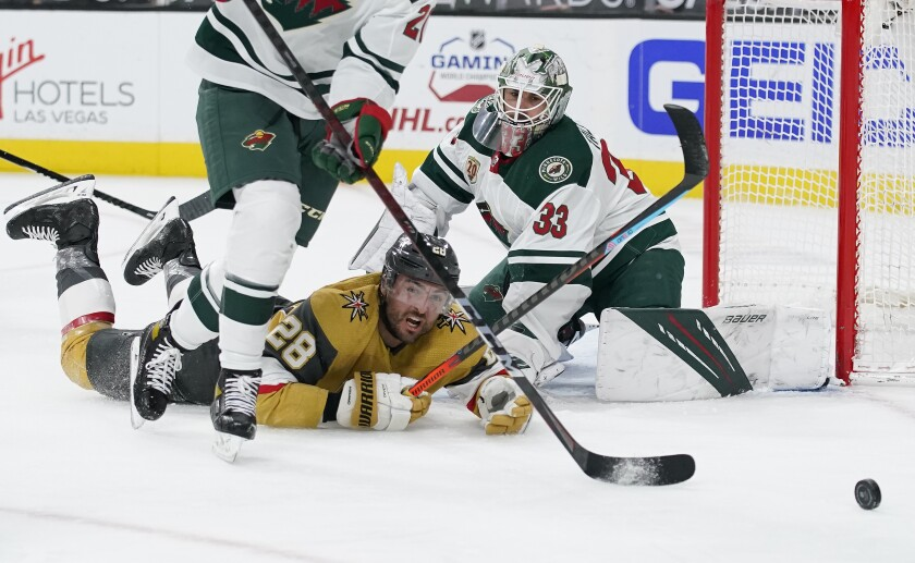 Vegas Golden Knights left wing William Carrier (28) falls into Minnesota Wild goaltender Cam Talbot (33) during the second period of an NHL hockey game Saturday, April 3, 2021, in Las Vegas. (AP Photo/John Locher)