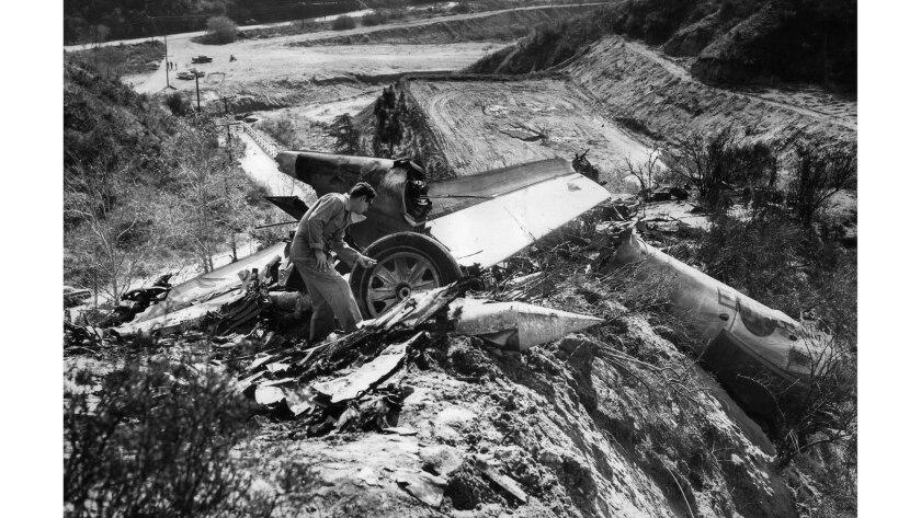 Jan. 31, 1957: Staff Sgt. Alvin Hidalgo of the Van Nuys Air National Guard checks through wreckage o