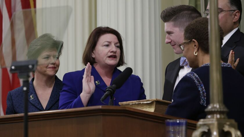 Jennifer LeSar, left, has had an increase in her affordable housing consulting business since her spouse, Senate President Pro Tem Toni Atkins (D-San Diego), center, has increased her power in the Legislature. The pair is seen here at Atkins' 2014 swearing in as Assembly speaker.