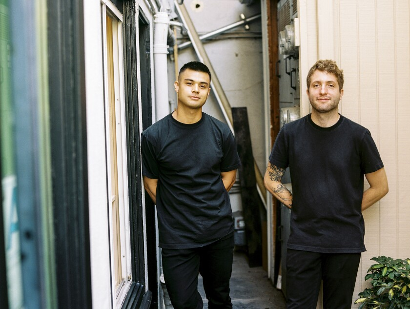 Two young men dressed all in black stand between buildings.