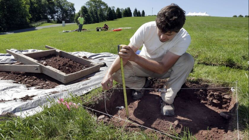 Paul Brown, of the Public Archaeology Facility at Binghamton University, measures a dig at the site of the original Woodstock Music and Art Fair in Bethel, N.Y.