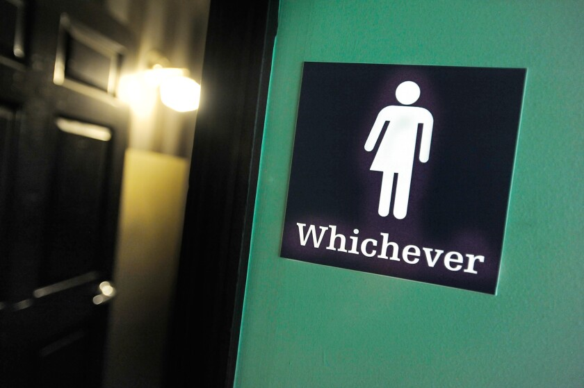 A gender-neutral sign is posted outside a bathroom at Oval Park Grill in Durham, N.C., in May.