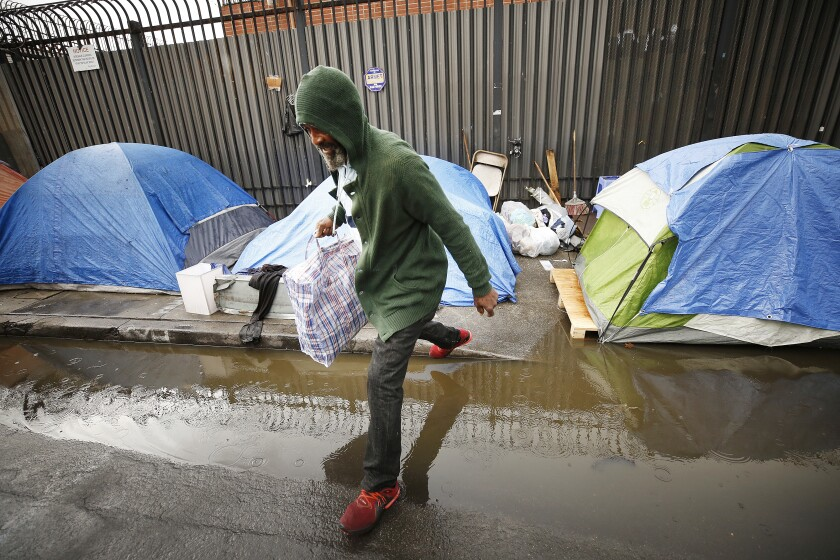 John Gunn leaps over water at his tent in skid row on Wednesday
