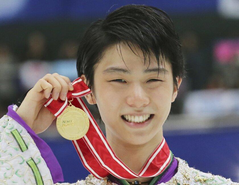 Japan's Yuzuru Hanyu poses with his gold medal during an award ceremony at the NHK Trophy figure skating in Nagano, central Japan Saturday, Nov. 28, 2015. (AP Photo/Koji Sasahara)