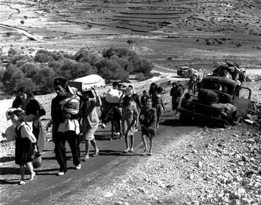 "FILE - In this November 4, 1948 file photo, Arab refugees stream from what was then Palestine, on the road to Lebanon in northern Israel to flee fighting in the Galilee region in the Arab-Israeli war. An Israeli high school principal has been summoned for a hearing by the country's Education Ministry for using a textbook presenting the Palestinian narrative about events surrounding Israel's creation in 1948, officials said Friday, Oct. 1, 2010. Israeli Jews celebrate 1948 as the year of their independence, while Palestinians and Israel's Arab citizens mourn what they call ""al-naqba"", the catastrophe, the year of their defeat and mass exodus. (AP Photo, File)"