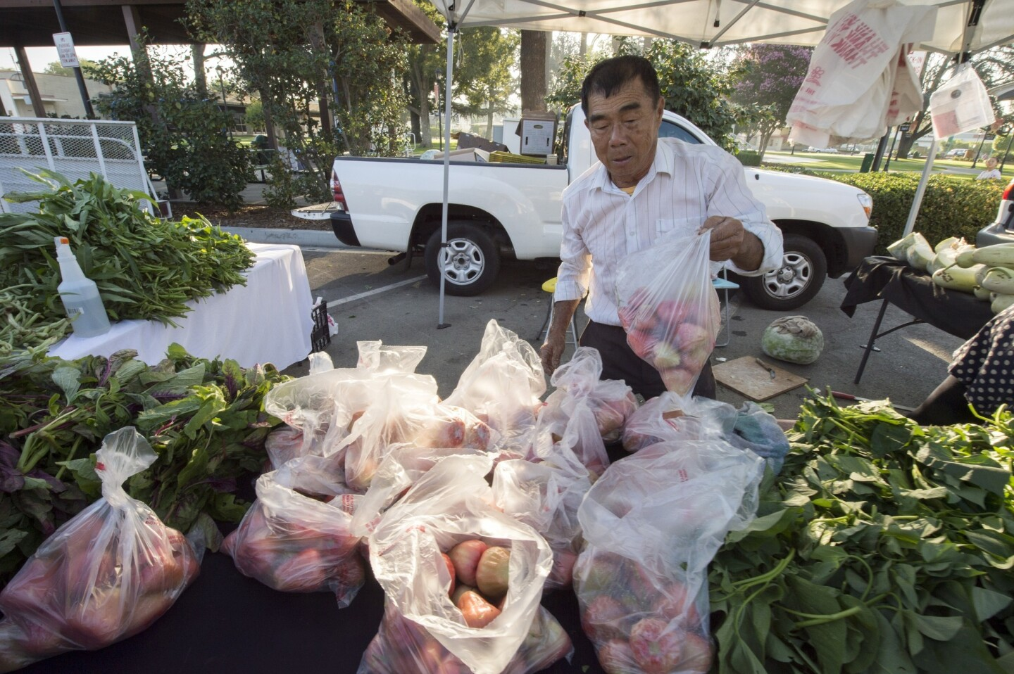 Lung Ke Wu sells wax apples, foreground, and many Asian vegetables at the Temple City farmers market.