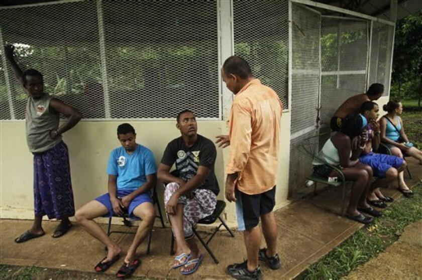 In this July 3, 2012 photo, Cuban migrant Mayra Reyes, sitting fourth from right, gathers with other Cubans with whom she traveled as they rest at a shelter along with another group of migrants from Bangladesh, after being found by Panamanian border police in the Darien province in Meteti, Panama. Panamanian authorities began noticing five years ago that the Darien Gap, the only interruption in the Pan-American Highway, was being used by migrant smugglers, usually to move people from Asia and Africa. Panama's Public Safety Minister Jose Murillo says that the movement of people from Asia and Africa has tapered off but that hundreds of Cubans are now taking the arduous Darien Gap route toward the United States. (AP Photo/Arnulfo Franco)