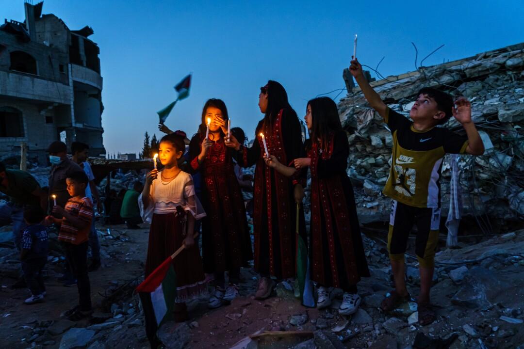 کودکان فلسطینی هنگام شرکت در مراسم نایب شمع در شهر غزه شمع روشن می کنند و گریه می کنند.