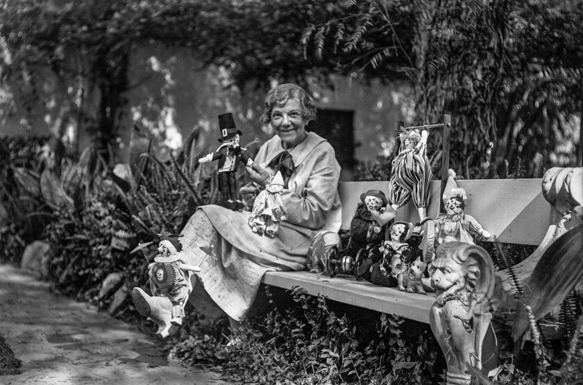 Harriet A. McCabe poses in a garden with dolls to be donated at Christmas.