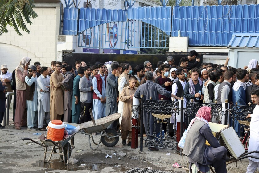 Afghans wait in long lines for hours to try to withdraw money in front of a bank in Kabul, Afghanistan on Monday.