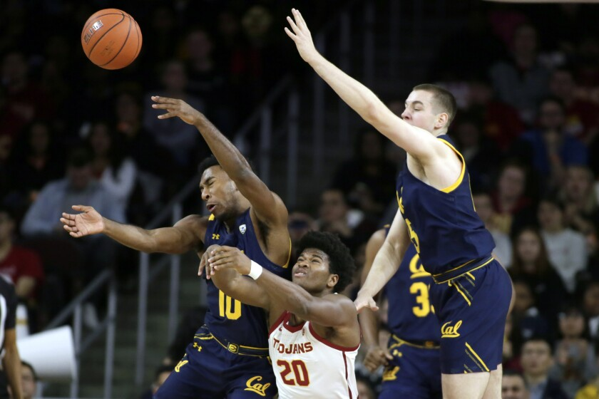 California guard Kareem South, left, battles USC guard Ethan Anderson, center, for the loose ball with forward Grant Anticevich, right, during the first half on Thursday at the Galen Center.