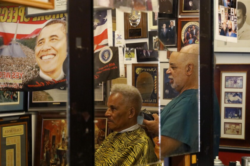 Lawrence Tolliver gives a haircut at his South L.A. barbershop