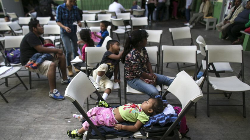 Children wait while their parents consult with attorneys and advocates at an immigration clinic in Tijuana.