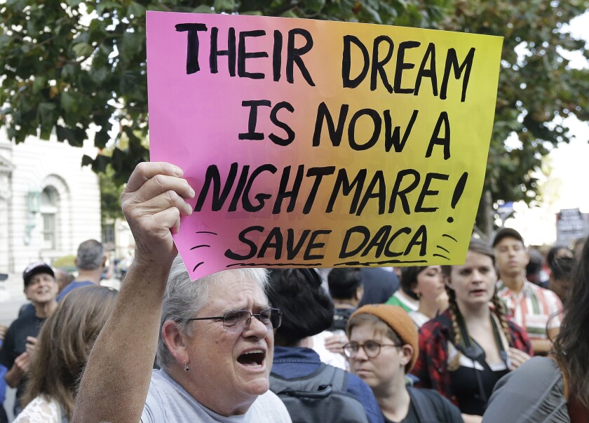 In this Sept. 15, 2017 photo, Judy Weatherly, a supporter of the Deferred Action for Childhood Arrivals (DACA) holds up a sign during a protest outside of the Federal Building in San Francisco.
