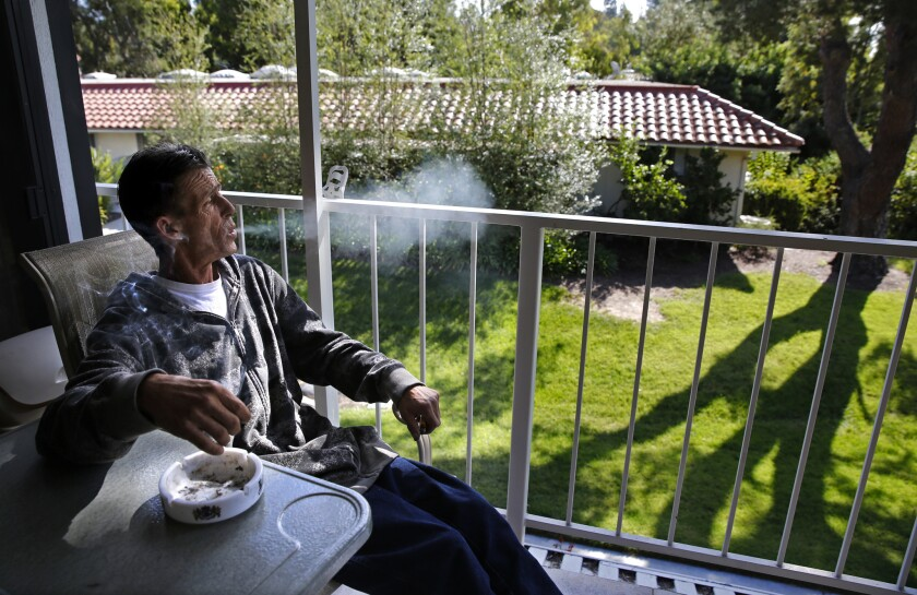 On the porch of his Laguna Woods home, Robert Evans, 52, who has cancer, smokes a medical marijuana cigarette. When he uses pot, he vomits less frequently.
