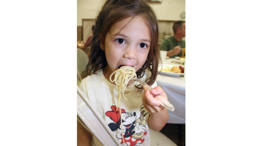 Tessa, Kjelstrom, 4, chows down on spaghetti without the sauce at the Boy Scout Troop 391 Fundraiser