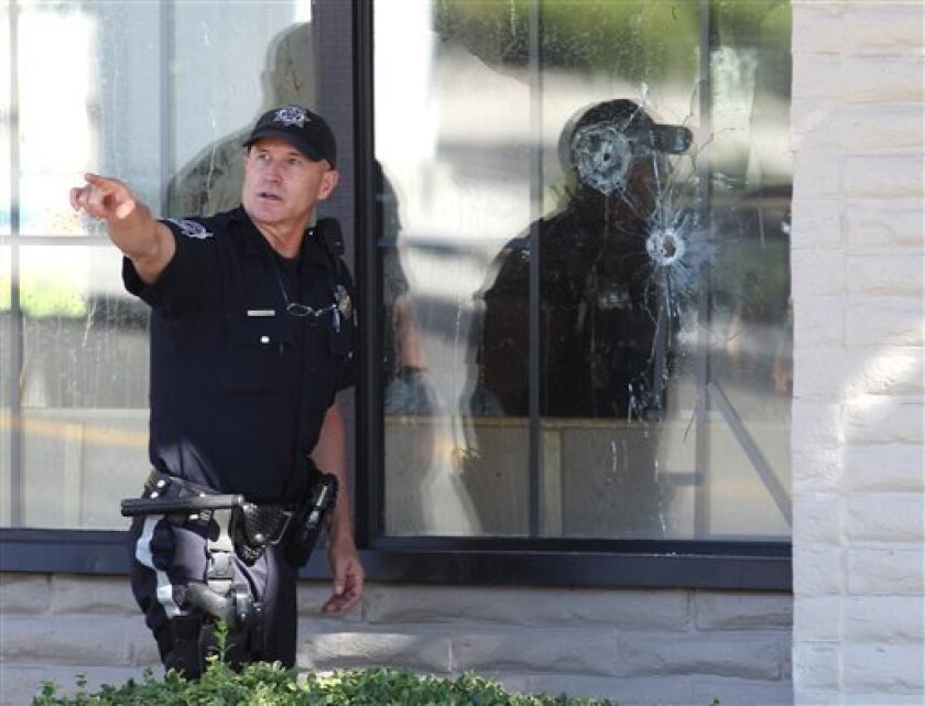 With bullet holes seen in a window, officers look for evidence at the scene of a shooting at an IHOP restaurant in Carson City, Nev. on Tuesday, Sept. 6, 2011. Seven people were wounded after a gunman opened fire at the restaurant, authorities said. (AP Photo/Cathleen Allison)