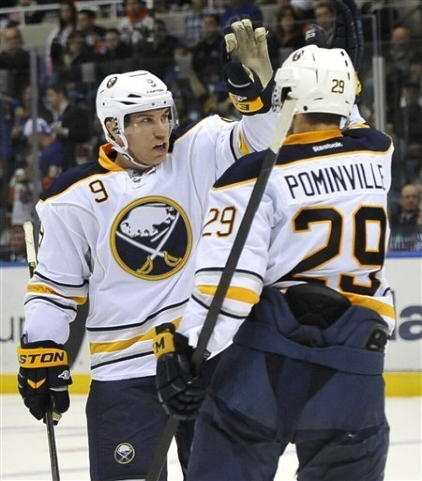 Buffalo Sabres' Derek Roy (9) celebrates his goal against New York Islanders goalie Al Montoya with teammate Jason Pominville (29) in the second period of an NHL hockey game on Saturday, Feb. 4, 2012, in Uniondale, N.Y. (AP Photo/Kathy Kmonicek)