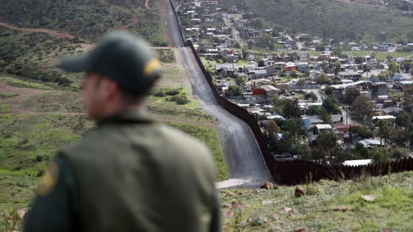 A Border Patrol agent looks on near a border wall that separates the cities of Tijuana, Mexico, and San Diego on Feb. 5.