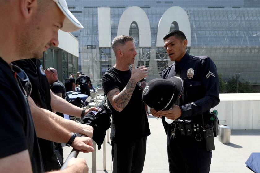 Police Constable Matthew Goodwin gives LAPD Officer Gabriel Flores a police helmet.