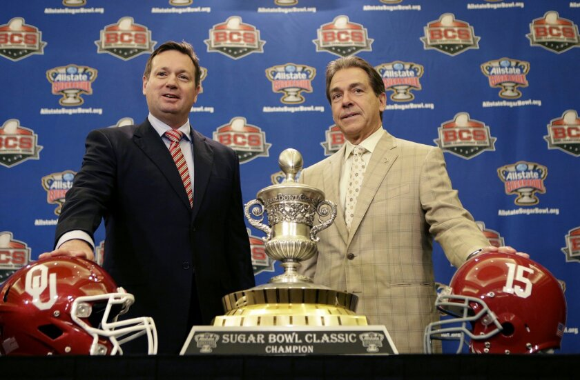 Alabama head coach Nick Saban, right, and Oklahoma head coach Bob Stoops pose with the Sugar Bowl trophy during an NCAA college football news conference in New Orleans, Wednesday, Jan. 1, 2014. Oklahoma takes on Alabama in the Sugar Bowl on Thursday. (AP Photo/Gerald Herbert)