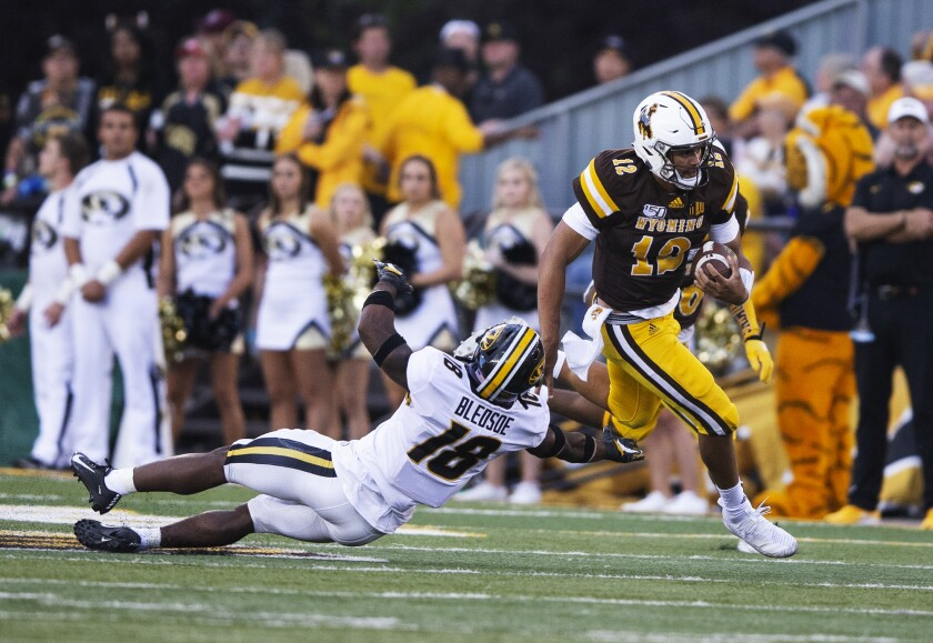 Wyoming quarterback Sean Chambers runs for a touchdown past Missouri defender Joshuah Bledsoe in the second quarter of the Cowboys' season-opening win.