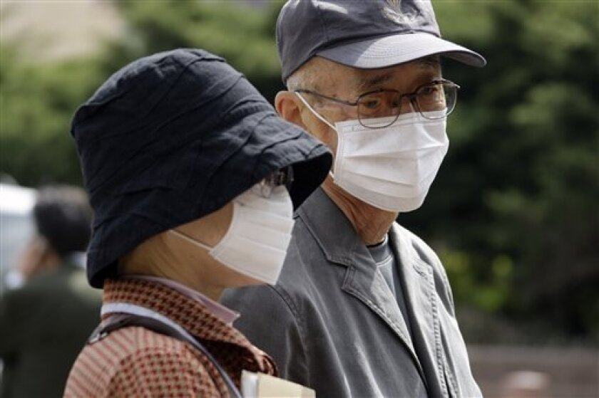 Tourists from Tokyo, Teluji Hanaoka, right, and his wife, Tsugiyo Hanaoka listen to Dr. Jonathan Fielding, not shown, director of public health for the county of Los Angeles, speaks about swine flu at the county hall of administration in downtown Los Angeles Wednesday, April 29, 2009. Swine flu fea