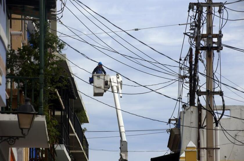 Un empleado trabaja restableciendo cables de electricidad dañados por el paso del huracán María en el Viejo San Juan (Puerto Rico). EFE/Archivo