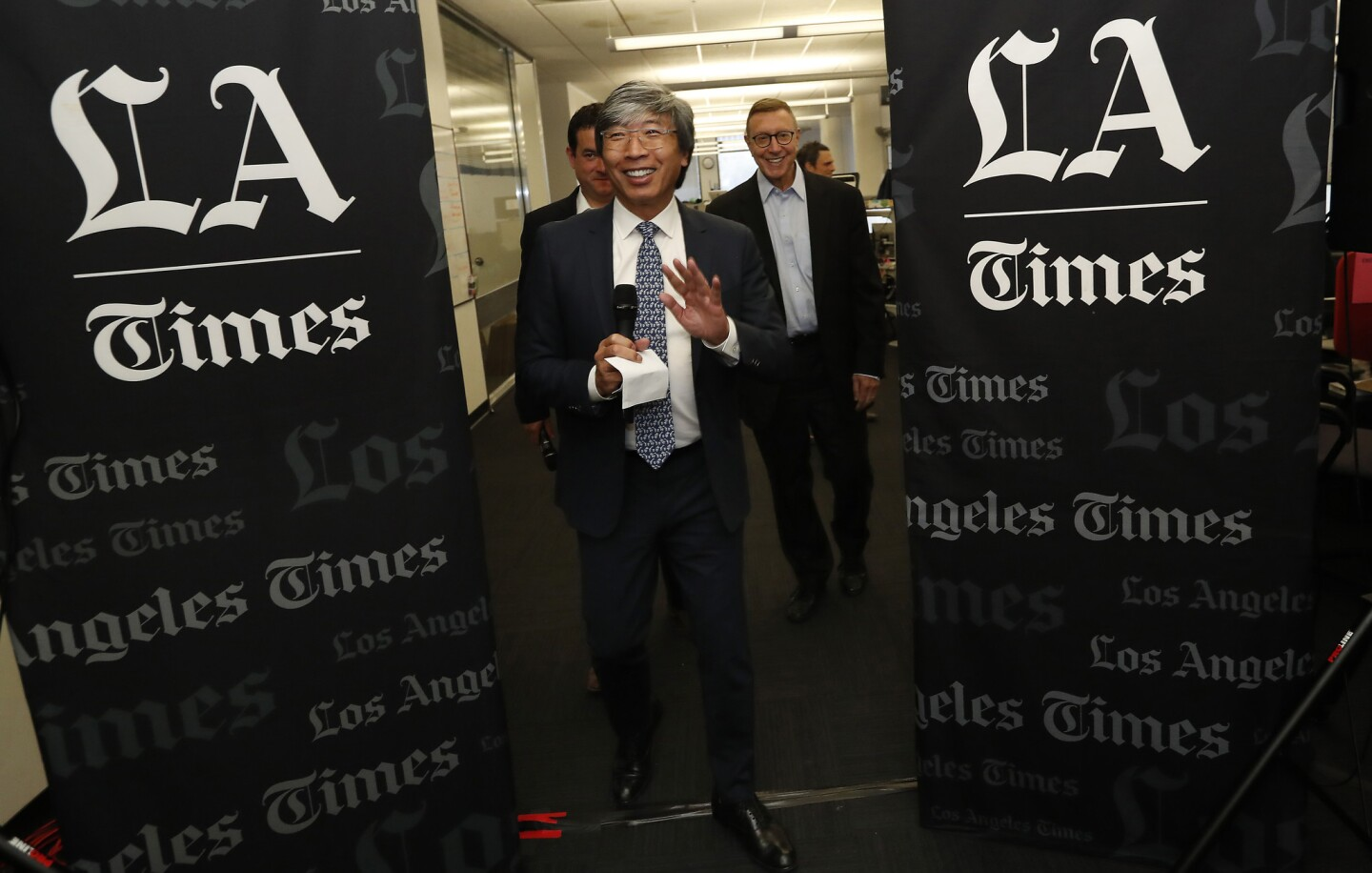 Dr. Patrick Soon-Shiong, foreground, in the Los Angeles Times newsroom Monday. He has taken the title of executive chairman of The Times and California Times, the new corporate moniker for the group of publications that he acquired. Behind him are Chris Argentieri, left, currently the general manager of The Times who will become chief operating officer of California Times, and Norman Pearlstine, who has been named executive editor of The Times.