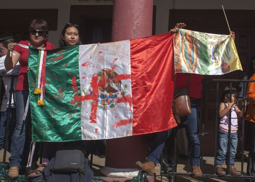 Activists display a Mexican flag painted to draw attention to the 43 missing students of the Ayotzinapa teachers school. The activists stationed themselves along the route Pope Francis took while in San Cristobal de Las Casas this week.