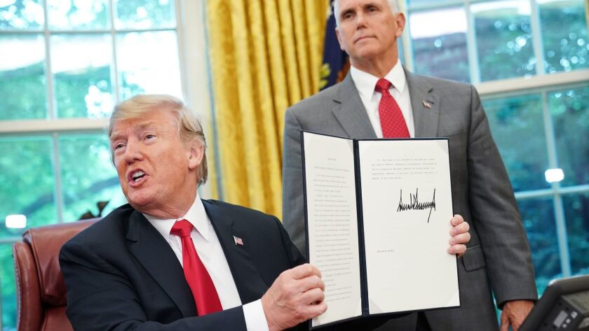 Watched by Vice President Mike Pence, President Trump shows an executive order ending his administration's family separation policy at the border.