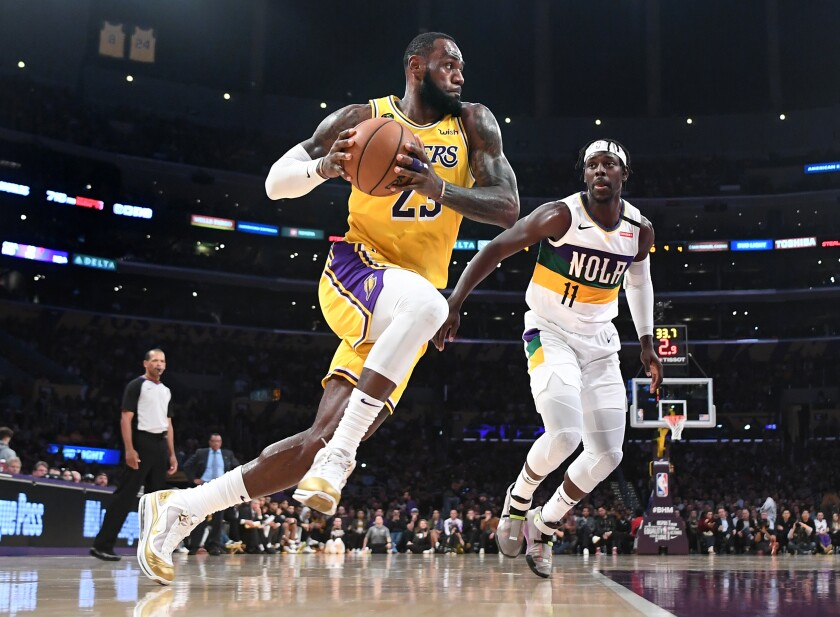 Lakers' LeBron James drives to the basket on New Orleans Pelicans' Jrue Holiday in the second quarter at Staples Center on Tuesday.