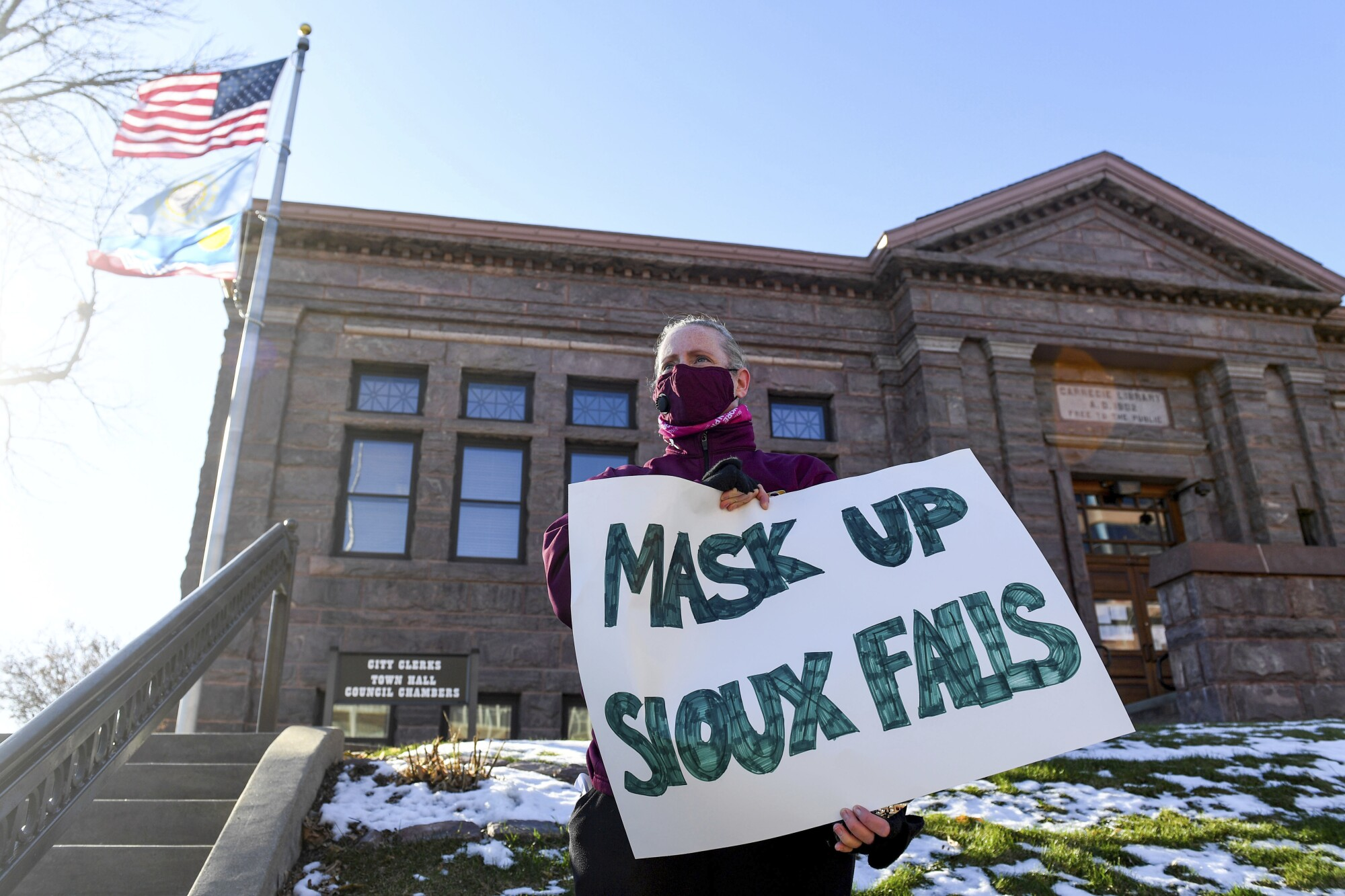 Jenae Ruesink holds a sign demanding a mask mandate from the city council in November in Sioux Falls, S.D.