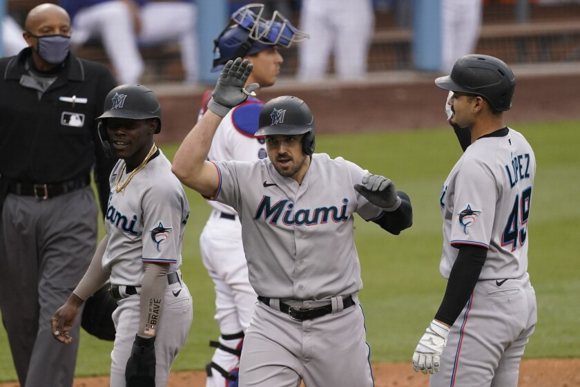 Miami Marlins' Adam Duvall (14) celebrates after hitting a home run during the fifth inning of a baseball game against the Los Angeles Dodgers Sunday, May 16, 2021, in Los Angeles. Pablo Lopez, right, and and Jazz Chisholm Jr., left, scored. (AP Photo/Ashley Landis)