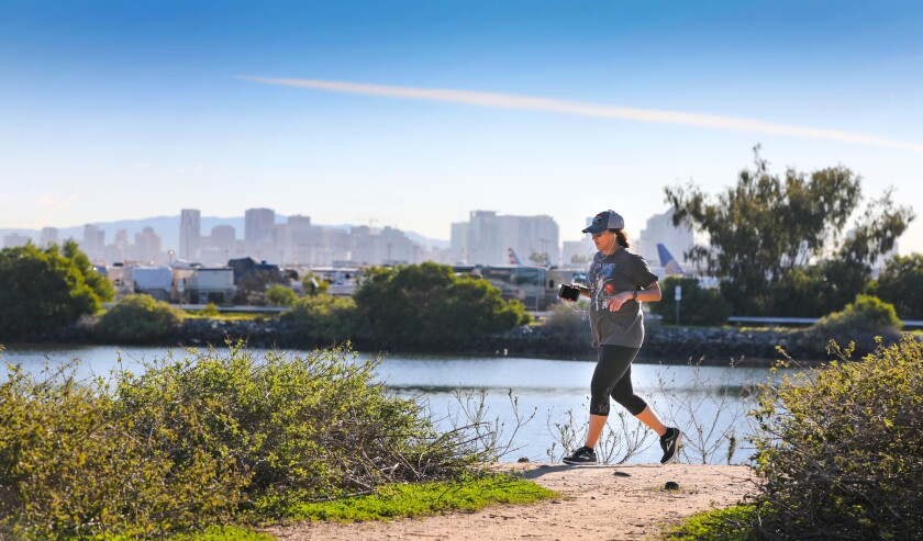 San Diego County unemployment stayed low at 2.8 percent in December. Pictured: With San Diego Bay, the San Diego International Airport and the San Diego downtown skyline as a backdrop, a visitor to Liberty Station jogs along a path that runs along San Diego Bay, January 7, 2020.