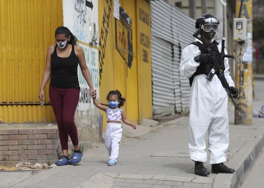 Un soldado con traje protector contra el coronavirus monta guardia en Bogotá.
