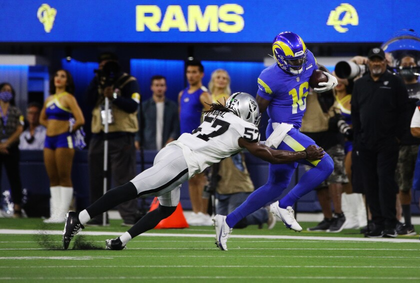 Rams QB Bryce Perkins (16) runs before just he's tackled by Raiders linebacker Asmar Bilal (57) in a preseason game.