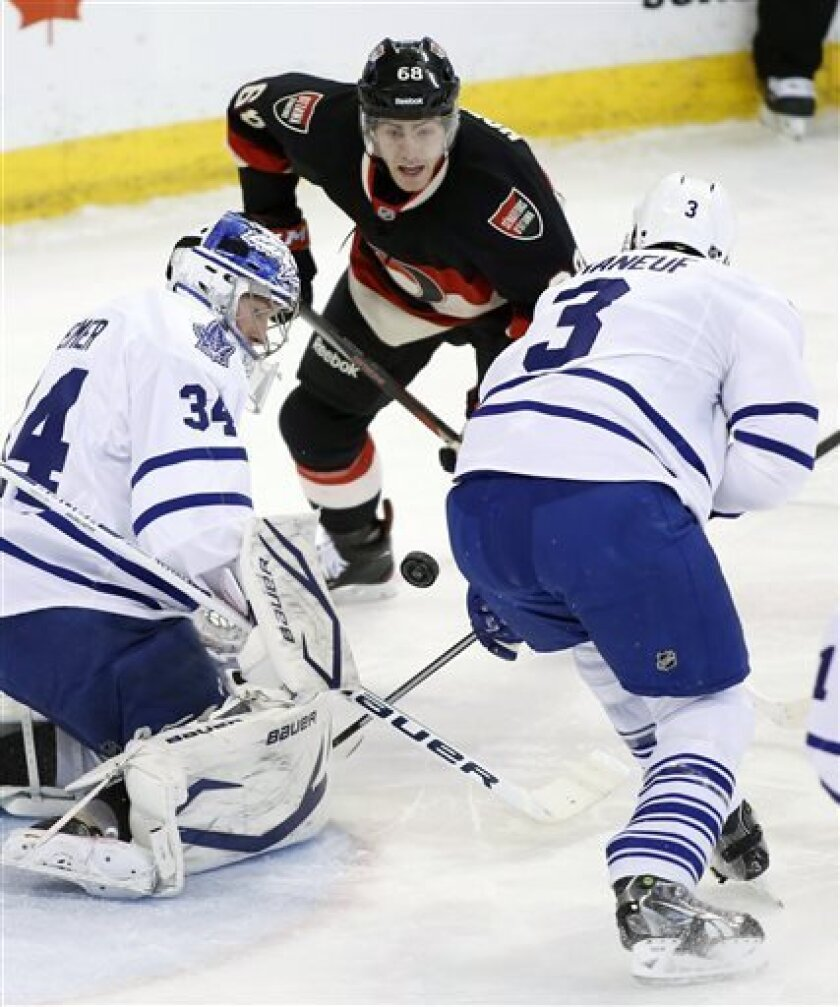 Toronto Maple Leafs goaltender James Reimer, left, Maple Leafs' Dion Phaneauf, right, and Ottawa Senators' Mike Hoffman watch the bouncing puck during first-period NHL hockey game action in Ottawa, Ontario, Saturday, March 30, 2013.  (AP Photo/The Canadian Press, Patrick Doyle)