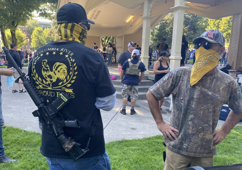 A man in a Proud Boys T-shirt carries a rifle and talks with another man at an outdoor gathering in September.