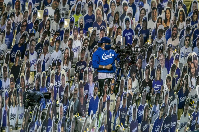 A camera operator works amid a sea of cardboard fans during a recent Dodgers game in Los Angeles.