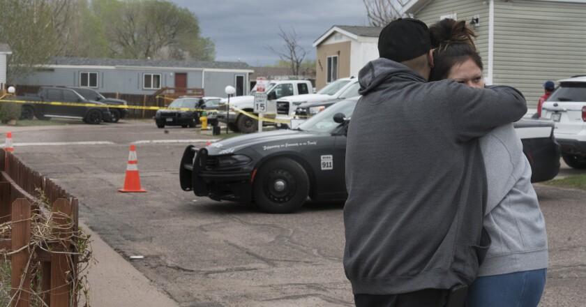 Un hombre y una mujer se abrazan en la calle frente al sitio donde ocurrió un tiroteo el domingo 9 de mayo de 2021