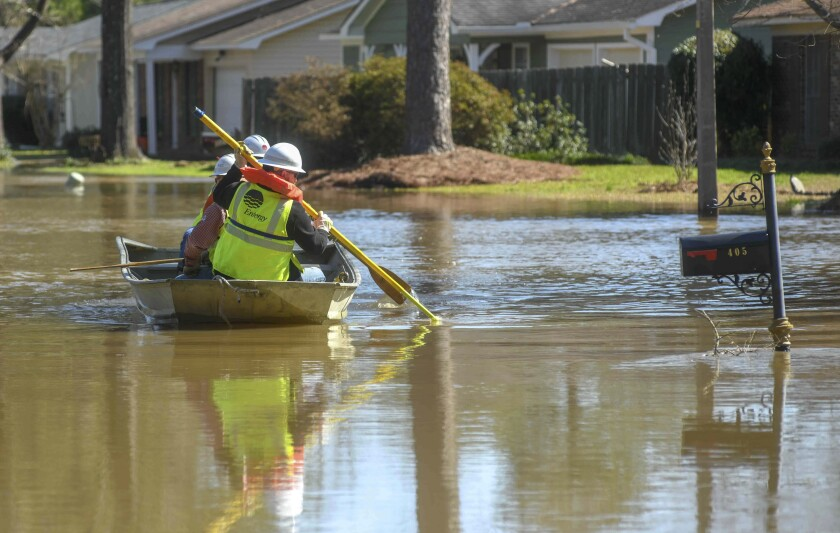 Energy workers use a boat to turn off power in flooded houses in the Canton Club Circle subdivision in northeast Jackson, Miss.