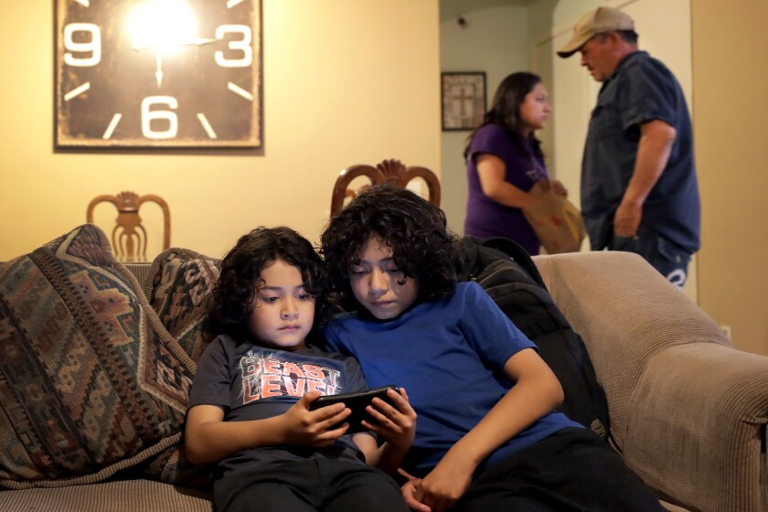 Joseph Diaz, 10, right, and his brother, John Diaz, 7, watch videos as their parents, Karina Ruiz and Humberto Diaz prepare dinner at their home, Thursday, Nov. 7, 2019 in Glendale, Ariz. Karina is in a program dating back to the Obama administration that allows immigrants brought here as children to work and protects them from deportation. The U.S. Supreme Court will hear arguments Tuesday, Nov. 12, about President Donald Trump's attempt to end the program, and the stakes are particularly high for the older generation of people enrolled in Deferred Action for Childhood Arrivals, known as DACA.(AP Photo/Matt York)